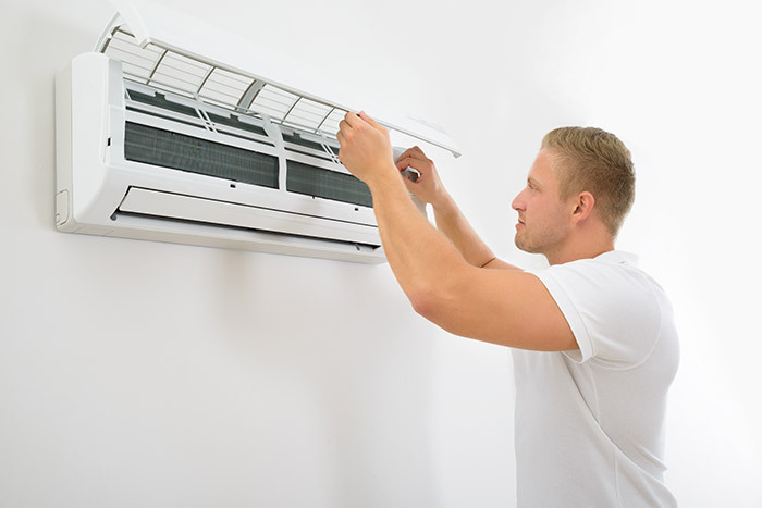 man inspecting air conditioning unit for problems